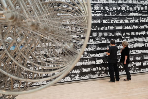 "Ai Weiwei and museum curator Sabine Eckmann examine ""The Odyssey,"" a massive frieze in his exhibition at the Mildred Lane Kemper Museum. In the foreground is a detail of ""Forever Bicycle,"" a sculpture made from 720 bicycles."