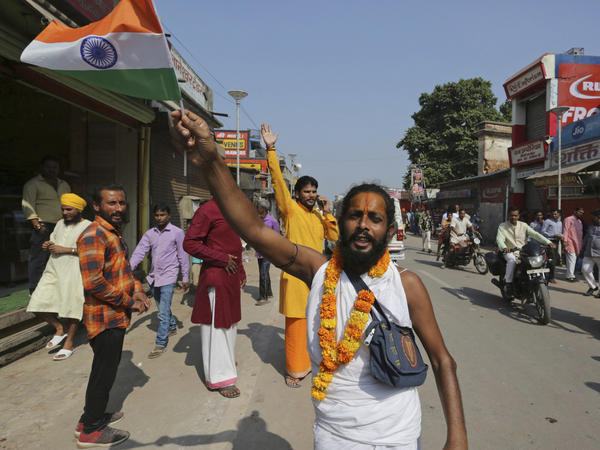 A Hindu devotee waves an Indian national flag and celebrates a verdict in a decades-old land title dispute between Muslims and Hindus, in Ayodhya, India, on Saturday.