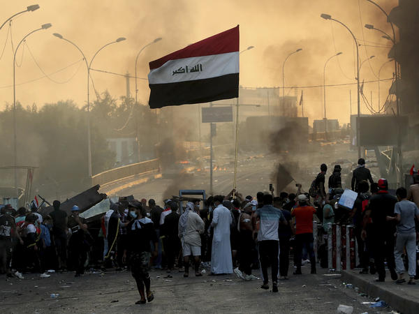 Anti-government protesters set fire and close streets during ongoing protests in Baghdad, Iraq on Saturday.