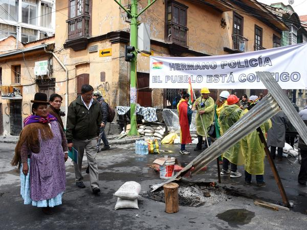"""People block a street with a banner reading """"brother policeman, the village is with you"""" near the main square in La Paz on Monday, the day after Bolivian President Evo Morales announced his resignation."""