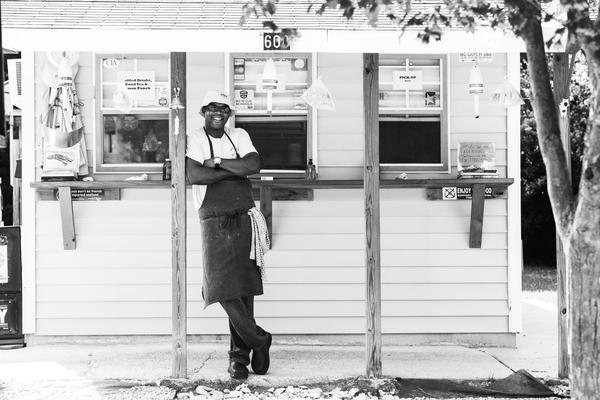 Chef Ricky Moore standing in front of the original Saltbox Seafood Joint on North Mangum Street in Durham.