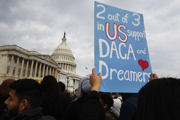 A woman holds up a sign outside the Capitol in support of the Deferred Action for Childhood Arrivals (DACA) program Tuesday, Dec. 5, 2017, on Capitol Hill in Washington.