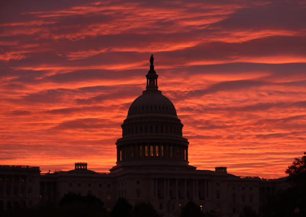 The sky turns to a fiery color as the sun begins to rise behind the U.S. Capitol building.