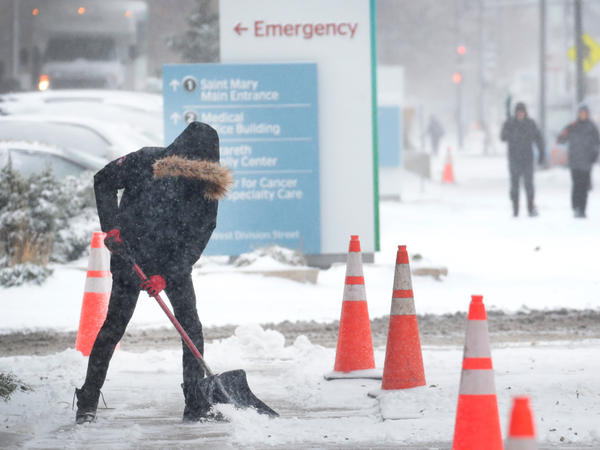 A worker shovels snow from a sidewalk in the Humboldt Park neighborhood of Chicago. Forecasters expect temperatures to drop around 10 degrees by Wednesday.