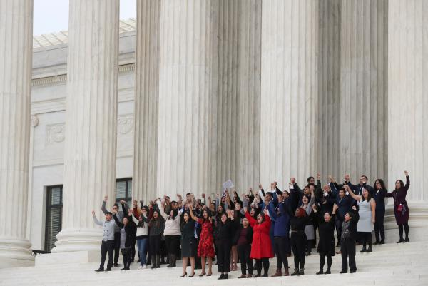 DACA plaintiffs clasp hands on the steps of the U.S. Supreme Court on Tuesday after justices heard oral arguments in the consolidation of three cases before the court regarding the Trump administration's bid to end the Deferred Action for Childhood Arrivals program.