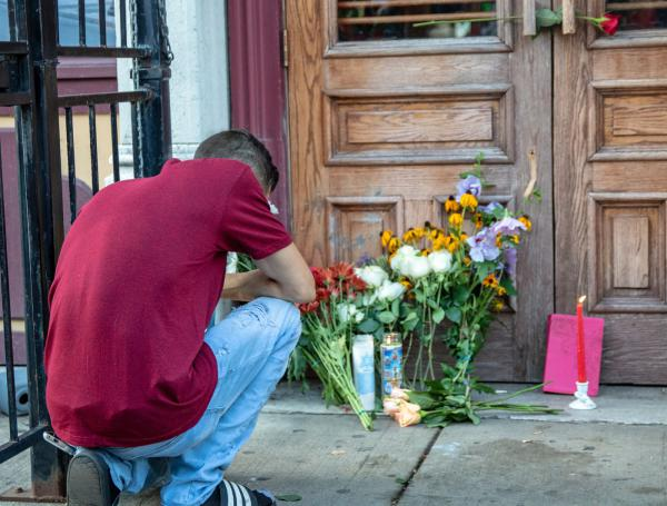 "A man kneels in front of a vigil for shooting victims in Dayton, Ohio, Aug. 5, 2019. This shooting was labeled a ""mass shooting"" by the media, but shootings with similar number of victims are often ignored. This article attempts to understand the difference."