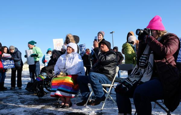 Fort Peck Assiniboine and Sioux council member, Patricia Iron Cloud, watches protestors make speeches against the Keystone XL pipeline ahead of a public meeting on October 29, 2019.