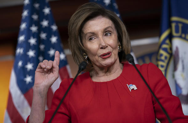 House Speaker Nancy Pelosi, D-Calif., talks to reporters after the first public hearing in the impeachment probe of President Trump. The House is looking into his effort to tie U.S. aid for Ukraine to investigations of his political opponents.