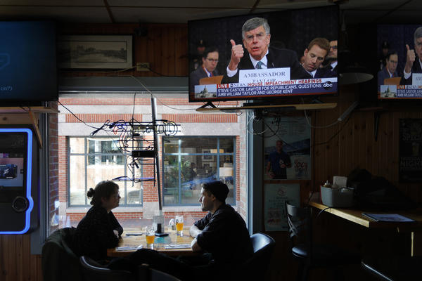 Olivia Tobin and her fiancé, Jordan Ashby, ignore the televised impeachment hearings playing on monitors at the Commercial Street Pub, Wednesday, Nov. 13, 2019, in Portland, Maine. (Robert F. Bukaty/AP)