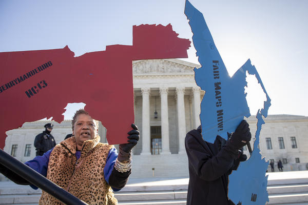 Activists opposed to partisan gerrymandering hold up representations of congressional districts from North Carolina, left, and Maryland, right, ahead of Supreme Court arguments last spring. The court ultimately decided that federal courts could not adjudicate partisan gerrymandering cases.