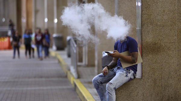 A Filipino man uses an e-cigarette outside a Manila mall in 2016. Philippines President Rodrigo Duterte announced Tuesday a total ban on vaping products.
