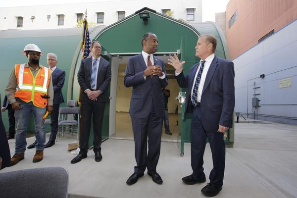 U.S. Department of Housing and Urban Development secretary Ben Carson, second from right, with Union Rescue Mission CEO, Andy Bales, far right, stand next to a temporary fabric structure meant to house homeless individuals, as he tours the Union Rescue Mission in downtown Los Angeles Wednesday, Sept. 18, 2019.