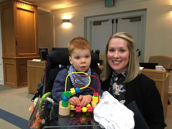 Lindsey Topping-Schuetz poses for a photo with her three-year-old son Owen before testifying about the challenges families face in obtaining state-paid developmental disabilities services.