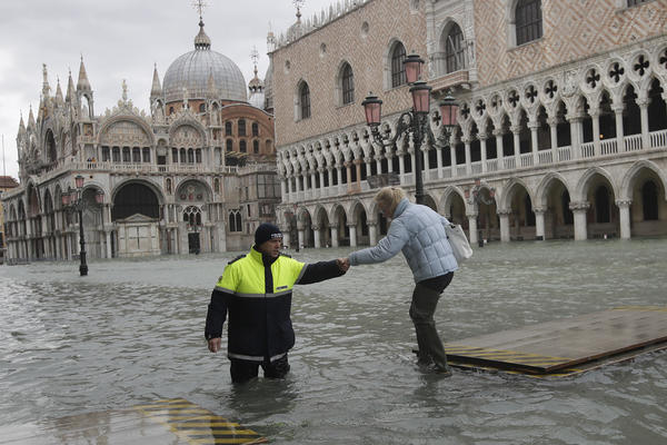 A city worker helps a woman who decided to cross St. Mark square on a gangway, in spite of prohibition, in Venice, Italy, Sunday, Nov. 17, 2019. (Luca Bruno/AP)