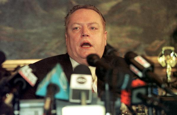 Surrounded by microphones at his office in Beverly Hills, pornography publisher Larry Flynt announces that paramours and former CIA and FBI agents delivered evidence showing about a dozen legislators had extramarital affairs.
