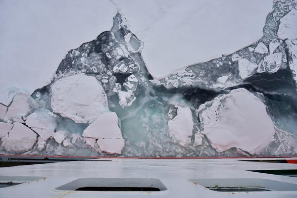 Chunks of ice float past the hull of the Akademik Fedorov as the ship moves through the southern edge of the Arctic Ocean ice pack.