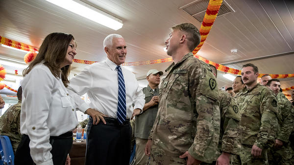Vice President Pence and his wife Karen Pence greet troops at a mess hall at Al Asad Air Base in Iraq on Saturday. At the base Pence spoke with Iraq's prime minister by phone because of security concerns.