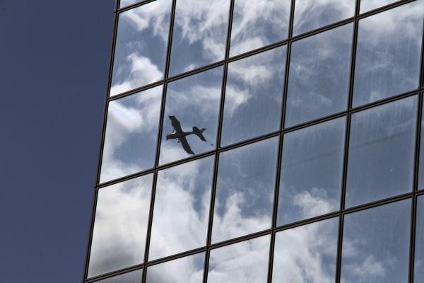 A small airplane flying over downtown Anchorage, Alaska, is reflected off the mirrored Atwood Building on Wednesday, Aug. 7, 2019.