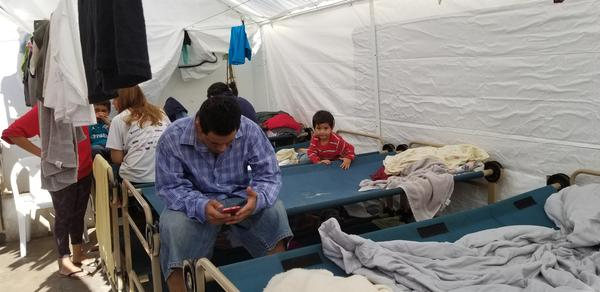 A man uses a mobile phone while at a shelter in Nuevo Laredo.