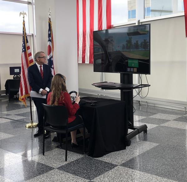 Gov. Mike DeWine watches a teenager practice driving through the virtual assessment.