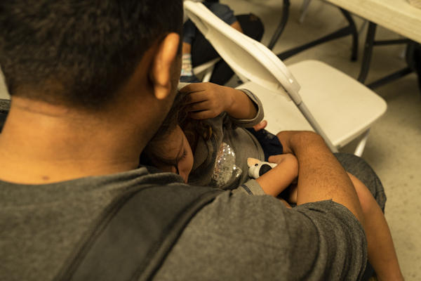 A migrant father holds his child in Laredo.