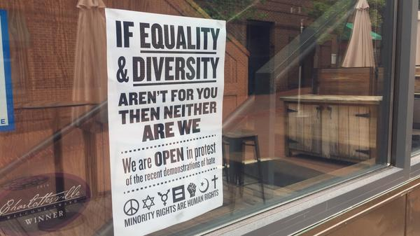 """Several downtown stores have put up signs and placards declaring: """"This is Our Town"""" and """"If Equality and Diversity Aren't for You, Then Neither Are We."""""""