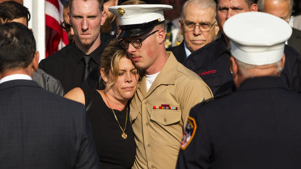 Erika Starke, left, is comforted by her son, Michael Haub, as they attend a second funeral service for New York Fire Department firefighter Michael Haub, in Franklin Square, N.Y. The New York City medical examiner identified more of his remains recovered at ground zero.
