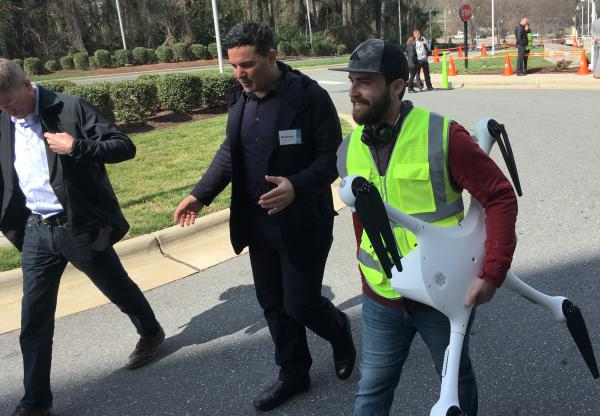 Matternet CEO Andreas Raptopoulos walks next to an operator carrying a drone used to deliver medical specimens after a flight in March at WakeMed Hospital in Raleigh, N.C.