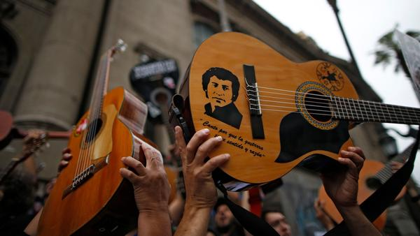 "Chilean singer-songwriter Víctor Jara is depicted on the guitar of a protester in Santiago. Jara's song, ""El Derecho de Vivir en Paz"" was sung by a crowd of demonstrators on October 25, 2019."