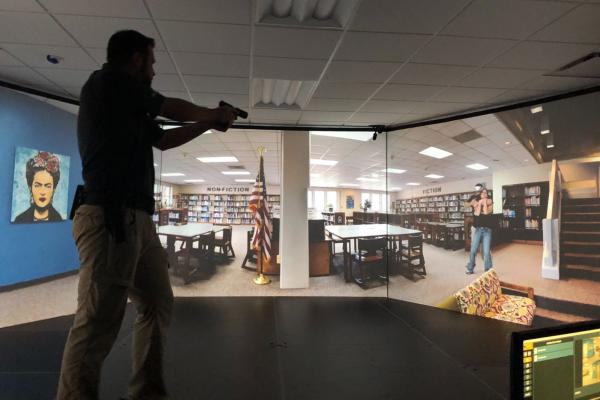 Jerico Lowery, an SRO for Pinecrest High School in Moore County, North Carolina, steps onto VirTra's stage at the Samarcand Training Facility. He's using a laser gun to shoot at the virtual gunman.