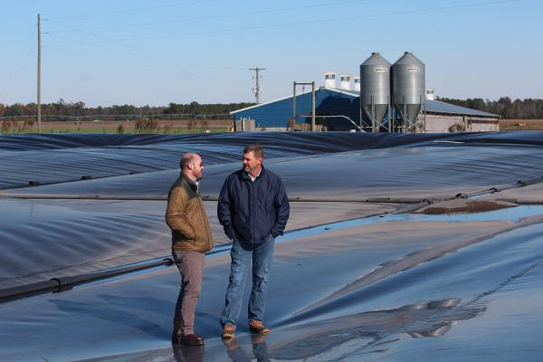 Ryan Childress (left), Dominion Energy's director of gas business development, and Kraig Westerbeek, an executive at pork producer Smithfield Foods, stand on a plastic-covered manure pond in North Carolina.