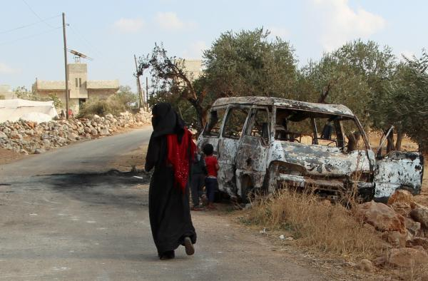 A woman walks past a wrecked van near the northwestern Syrian village of Barisha. Local residents and medical staff tell NPR that noncombatant civilians were killed and injured in the van the night of the U.S. raid on the compound of ISIS leader Abu Bakr al-Baghdadi.