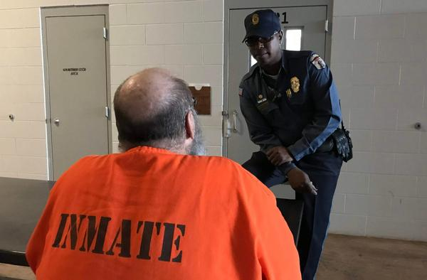 A corrections officer talks with an inmate at the Joseph Harp Correctional Center in Lexington.