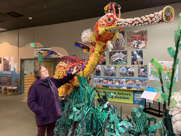 In her gallery in Bandon, Ore., Angela Haseltine Pozzi stands next to an enormous sea dragon sculpted from plastics found on Oregon's beaches that are normally famous for being pristine and wild.