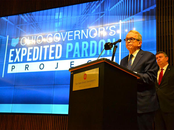 Gov. Mike DeWine, with Dean Christopher Peters of the University of Akron School of Law behind him, announces his expedited pardon process at Ohio State.