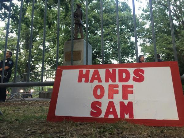 A sign in support of the Silent Sam statue rests near the monument on Tuesday, August 22, 2017 as hundreds of protesters gathered in opposition of the statue.