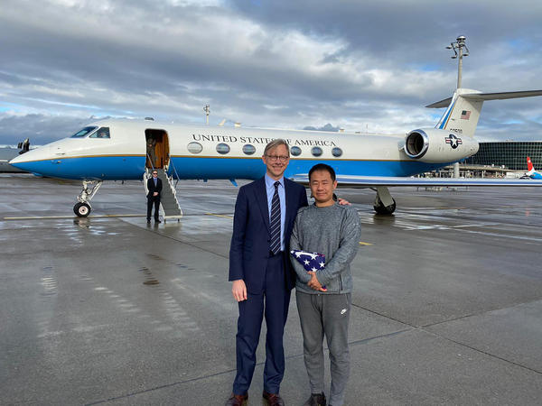 In a photo provided by the U.S. State Department, U.S. special representative for Iran Brian Hook stands with Xiyue Wang in Zurich, Switzerland on Saturday.