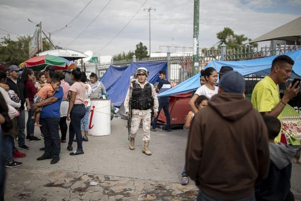 A Mexican soldier patrols the makeshift migrant camp at the base of Paso del Norte International Bridge in Ciudad Juarez.