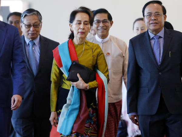 In this photo provided by the Myanmar State Counsellor Office, Aung San Suu Kyi, center, departs from Naypyitaw International Airport in Naypyitaw, Myanmar on Sunday.