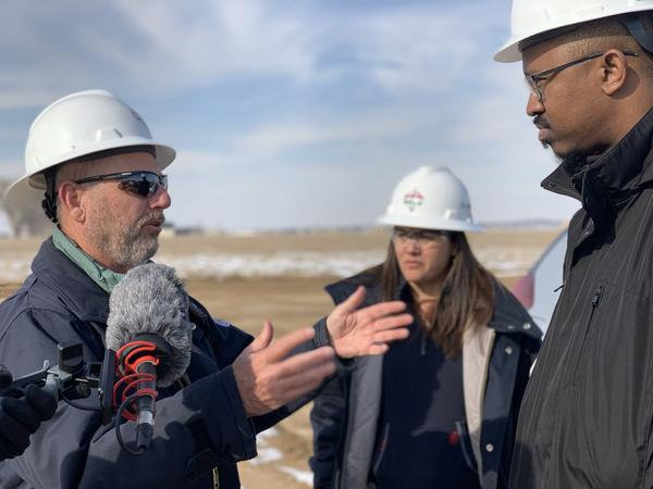 Host Joshua Johnson speaking with Mike Eberhard, SRC's chief operating officer, at an oil and natural gas extraction site in Weld County, Colorado. (Photo Credit: Amanda Williams/WAMU)