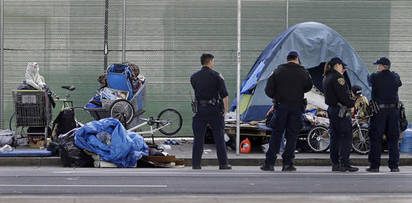 San Francisco police officers wait while homeless people collect their belongings in San Francisco. Nearly a quarter of the country's homeless population lives in California.