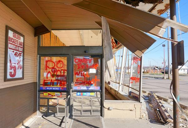 """A sign at the heavily damaged Grocery Lane store issues a warning: """"Do Not Enter. Owner Inside. Will Shoot."""""""