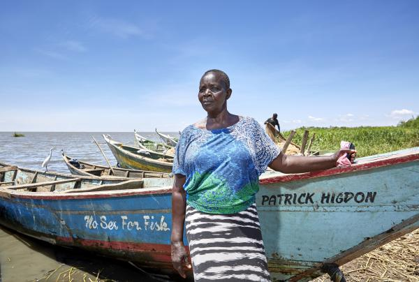 Justine Adhiambo Obura, chairwoman of the No Sex For Fish cooperative in Nduru Beach, Kenya, stands by her fishing boat. Patrick Higdon, whose name is on the boat, works for the charity World Connect, which gave the group a grant to provide boats for some of the local women.