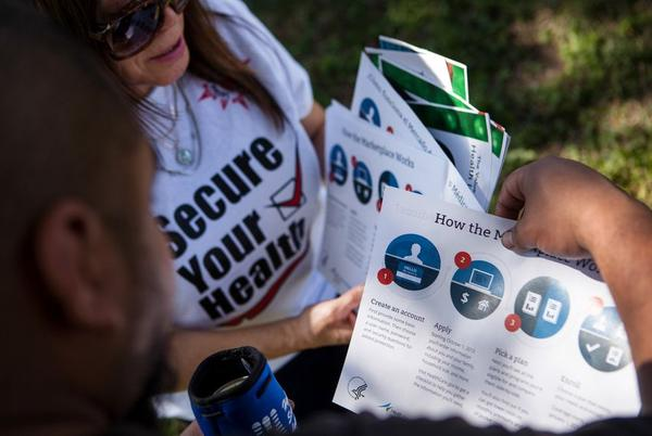 Jill Ramirez, the Director of Outreach for the Latino Healthcare Forum, passes out flyers and explains components of the American Care Act (ACA) to Jesse Zavala at a carshow and picnic at the Promiseland Church in Austin, Texas on Oct. 5, 2013.