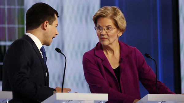 Democratic presidential candidate South Bend, Ind., Mayor Pete Buttigieg speaks with Sen. Elizabeth Warren, D-Mass., during a commercial break in the November Democratic presidential primary debate in Atlanta. They are back onstage Thursday in Los Angeles.