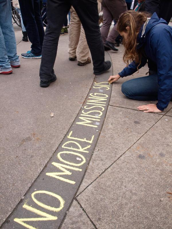 A woman uses chalk to write the words 'No more missing sisters' at Vancouvers Womens Memorial March in 2015.