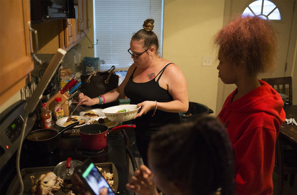 Regina Hartfield serves dinner for her children in their south St. Louis home. The state's Medicaid dropped her children from the program in late summer.