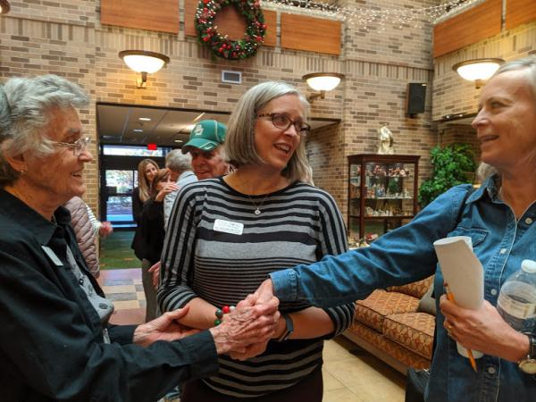 The director of the Grace Notes Community Choir clasps hands with two singers after their Christmas concert. One is a person living with dementia and the other is a caregiver.