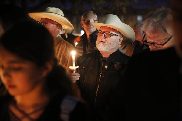 Stephen Willeford, center, who confronted and exchanged gunfire with the Sutherland Springs church shooter in 2017, joins church and community members gathered outside West Freeway Church of Christ for a candlelight vigil Monday night.