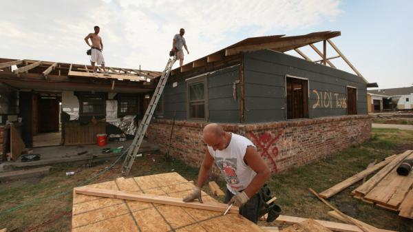 Anthony Owens (right) repairs the roof of a tornado-damaged home with James Davis (left) and Dwain Payne on July 30 in Joplin, Mo. All three men came up from Mobile, Ala., looking for work after the May 22 tornado that devastated Joplin, killing 160 people and destroying 7,500 homes and as many as 500 businesses.